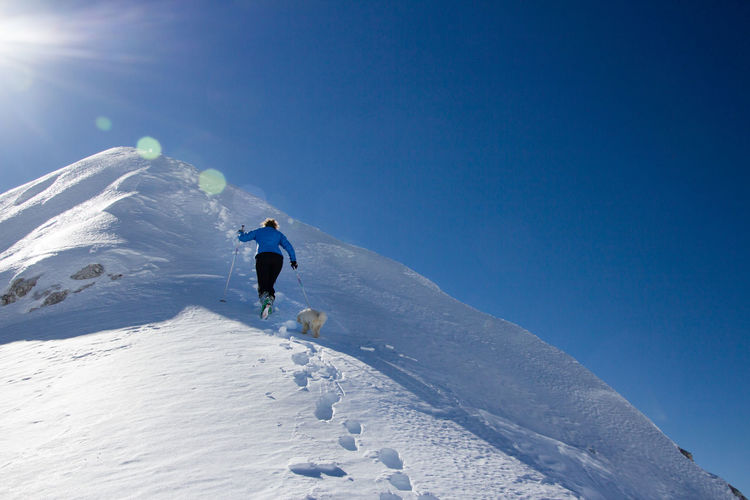 Woman with dog walking on snowcapped mountain against sky