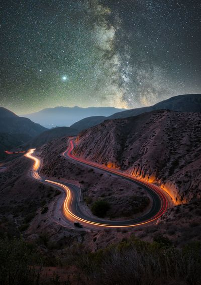 The colorful roads around the mountains reflect the stars