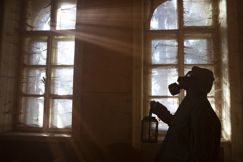 Side view of silhouette man holding window