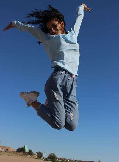 Woman Jumping Against Clear Blue Sky