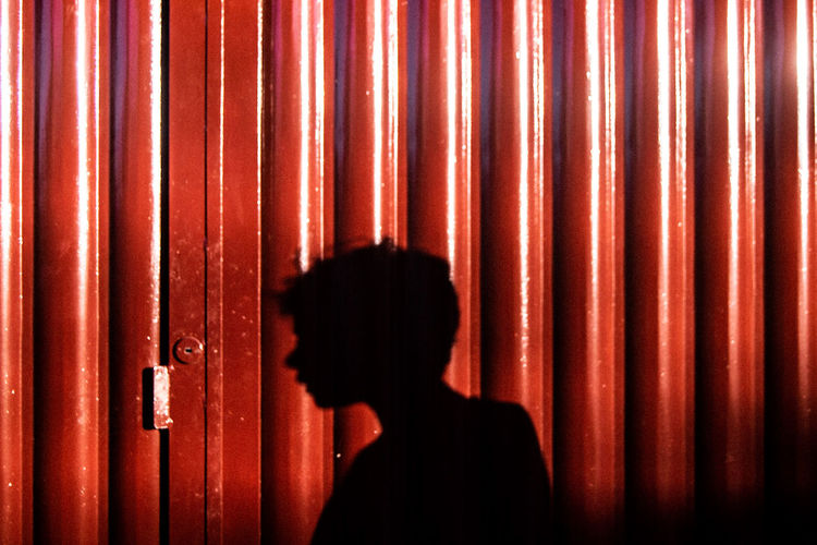 Shadow of man on brown corrugated iron