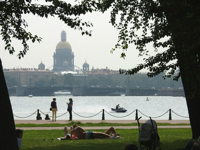 People relaxing at park in front of lake and buildings against clear sky