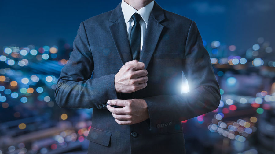 Midsection of man standing in illuminated city at night