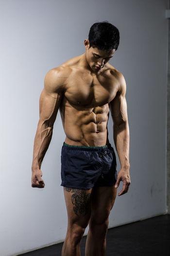Shirtless Muscular Man Standing Against Wall