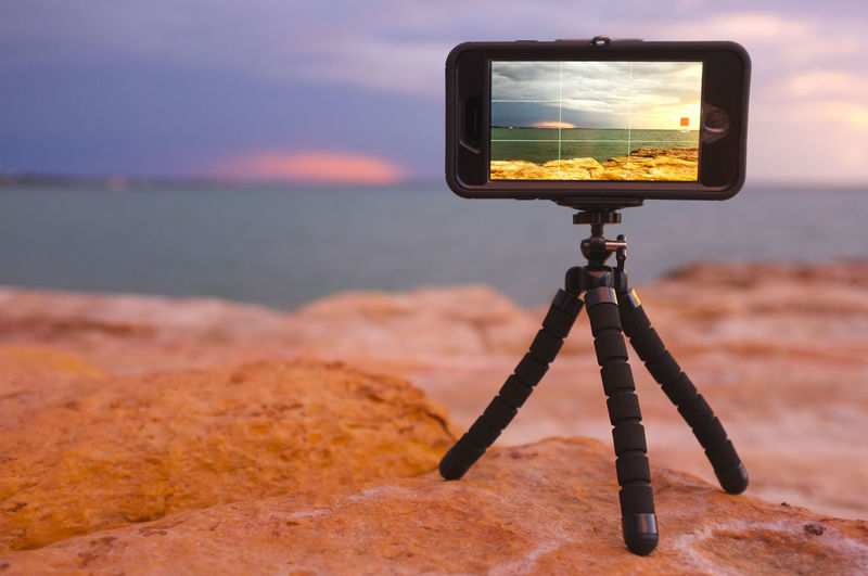 Mobile phone on a mini tripod recording a time-lapse at East Point in Darwin, Northern Territory, Australia. Technology Photography Themes Camera - Photographic Equipment Photographic Equipment Tripod Water Photographing Communication Sea No People Beach Focus On Foreground Wireless Technology Nature Sunset Screen IPhoneography Mobile Photography Mobile Video Memories Humanity Meets Technology