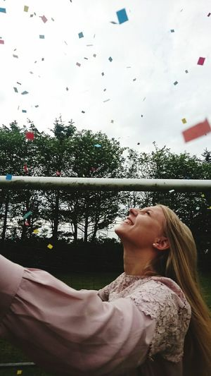 Close-Up Of Girl With Confetti Against Sky