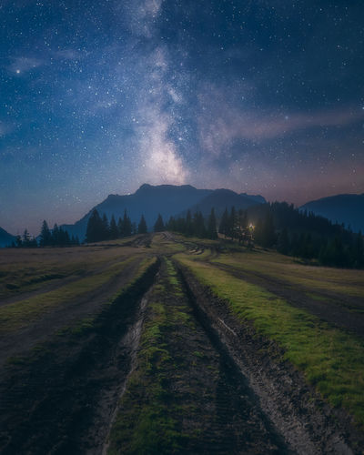 Empty road amidst field against sky at night