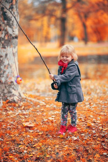 Autumn day in the park Autumn Imagination Orange Red Autumn Blond Hair Child Childhood Day Fishing Girl Orange Color Outdoors Park Park - Man Made Space Playing Toddler  Tree