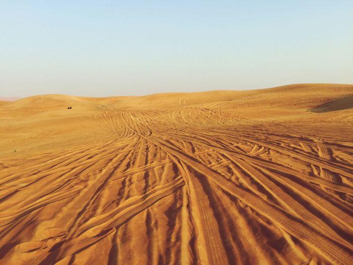 Tire Tracks On Desert Against Sky