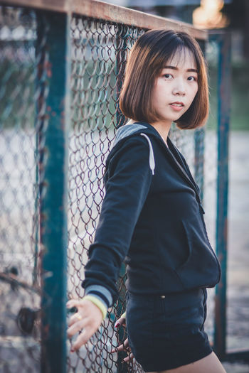 One Person Real People Looking At Camera Three Quarter Length Fence Leisure Activity Portrait Standing Lifestyles Day Casual Clothing Barrier Focus On Foreground Boundary Smiling Chainlink Fence Women Sport Outdoors Hairstyle Bangs Teen