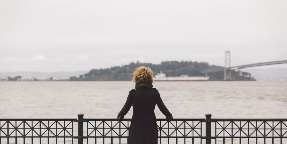Rear view of woman with curly hair standing by railing against lake