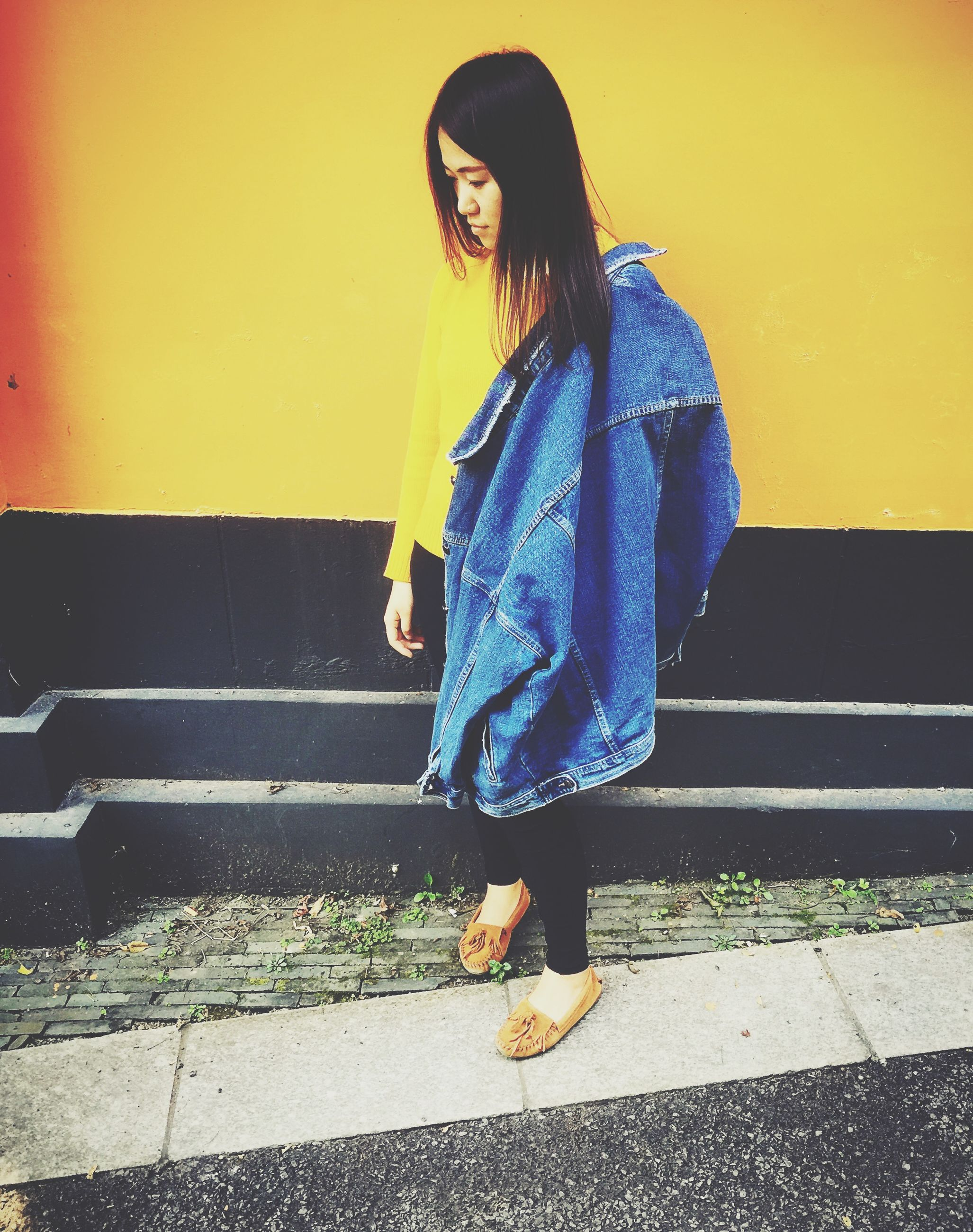 casual clothing, lifestyles, standing, young adult, person, full length, leisure activity, young women, front view, three quarter length, wall - building feature, side view, jacket, fashionable, long hair, looking away, yellow, holding