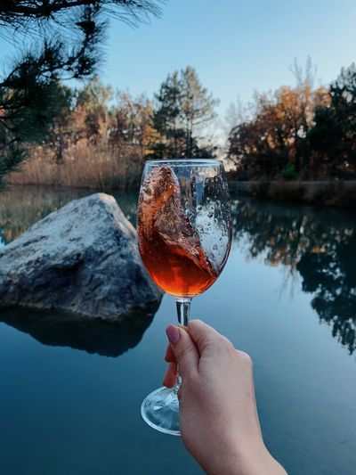 Person holding wineglass against lake