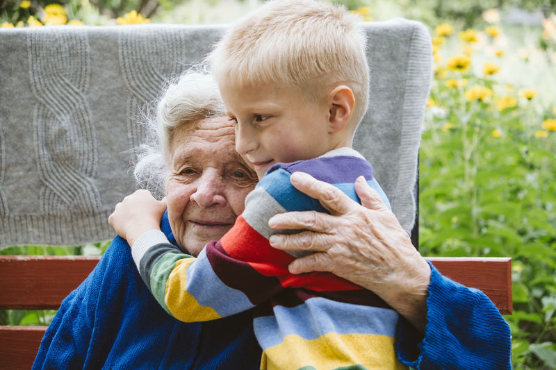 Grandmother embracing grandson while sitting on bench outdoors