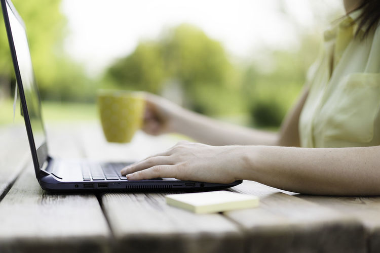 Midsection of woman using laptop outdoors