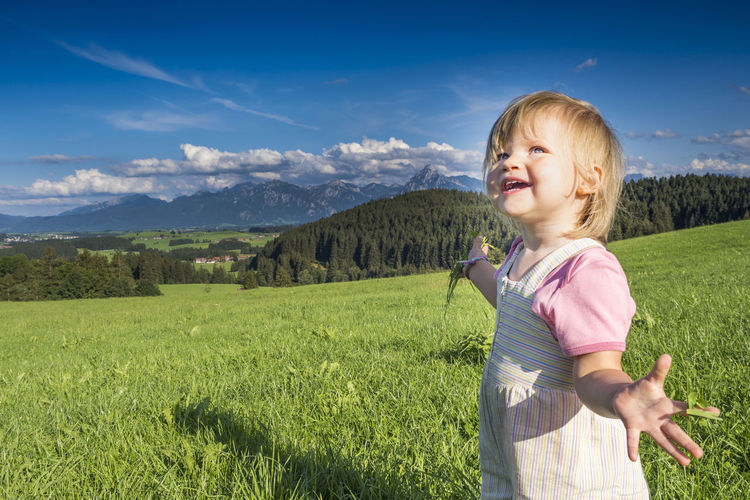 Smiling cute girl gesturing while standing on grass against sky