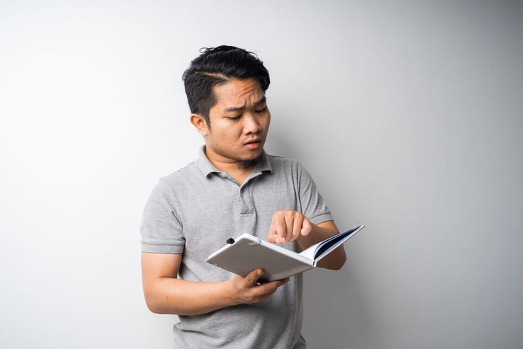 Man looking away while standing against white background