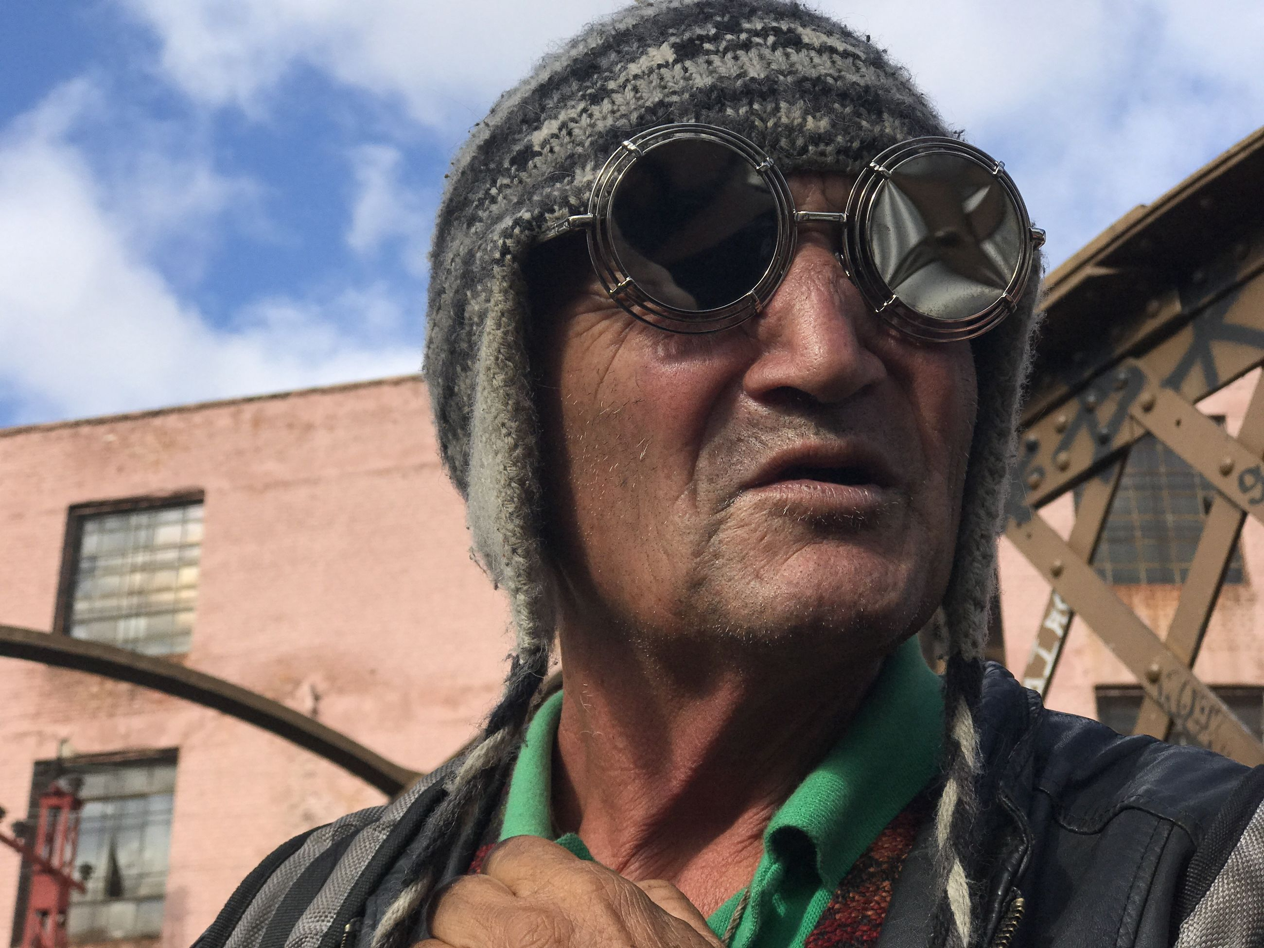 real people, one person, mid adult men, headshot, mid adult, portrait, outdoors, mature men, front view, day, sunglasses, low angle view, looking at camera, jacket, built structure, building exterior, lifestyles, sky, mature adult, cloud - sky, architecture, smiling, close-up, young adult, warm clothing, people