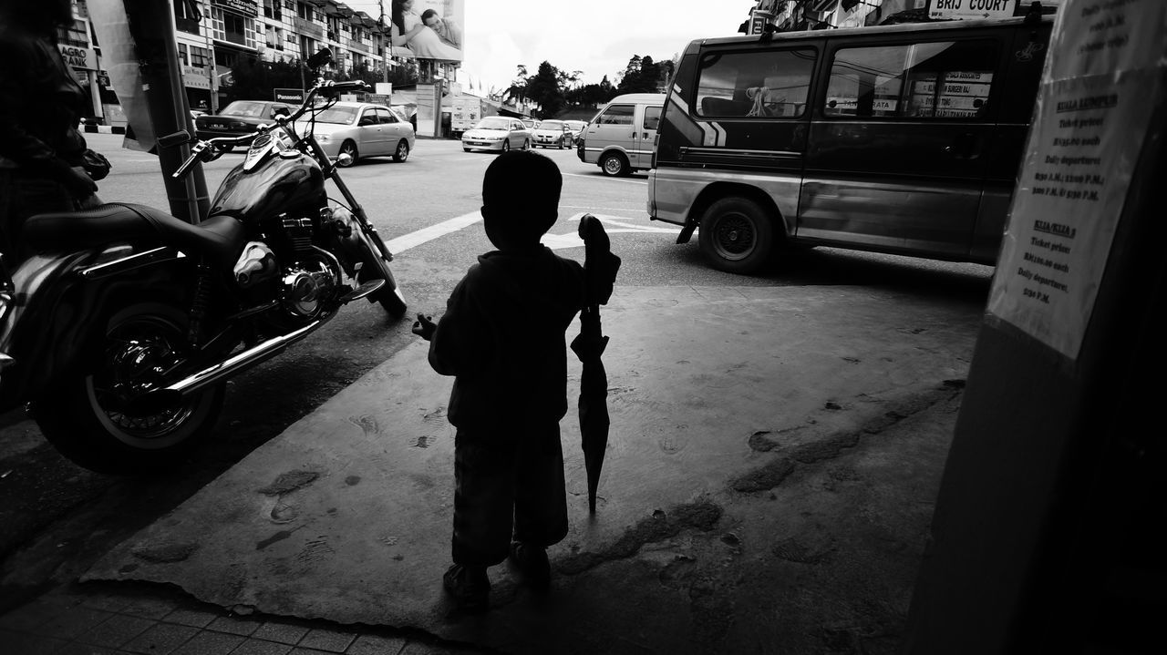 Rear view of boy standing with umbrella on street