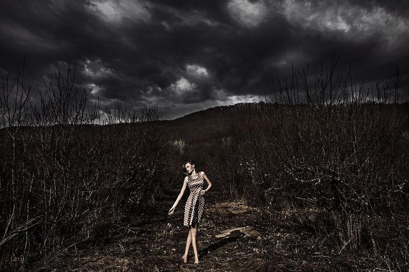 Woman standing on field against dark cloudy sky