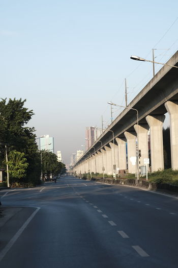 Road leading towards city against clear sky
