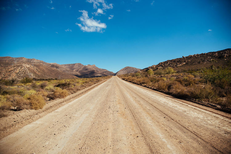Dirt road leading towards mountains against blue sky