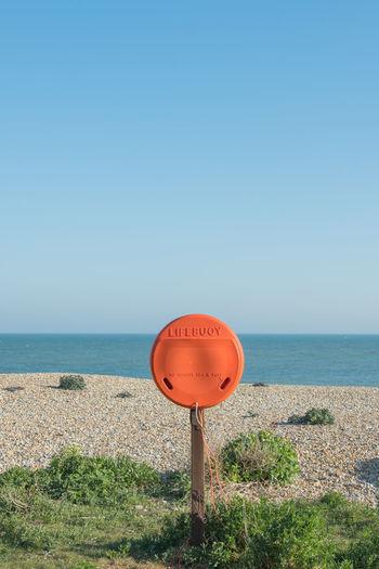 Bright orange lifebuoy on eastbourne beach