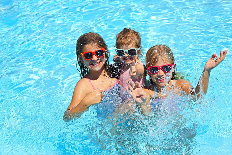 High angle view of siblings enjoying in swimming pool