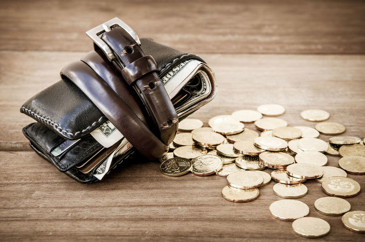 Wallet tied with belt and gold coins on wooden tabletop Business Economy Wallet Wooden Table Assets Bailout Banking Belt  Close-up Concept Currency Expenses Finance Gold Coins Income Liabilities Money Mortgage No People Savings Thrift Tied Up Tighten Tightening Wealth
