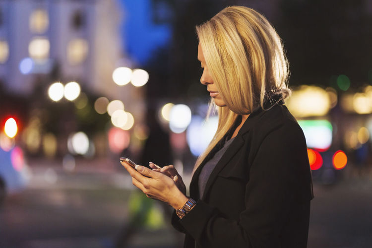Side view of woman using smart phone at night