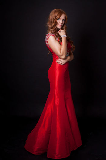 Portrait of beautiful woman wearing gown standing over black background