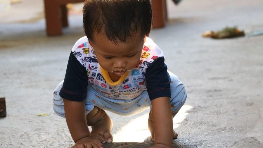 Full length of cute baby boy crouching on floor
