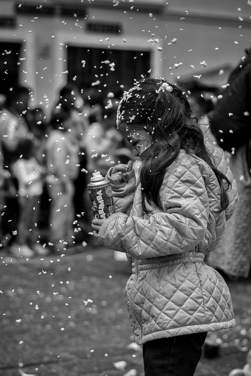 real people, lifestyles, leisure activity, focus on foreground, outdoors, casual clothing, one person, fun, bubble wand, standing, motion, women, young women, happiness, water, day, young adult, nature