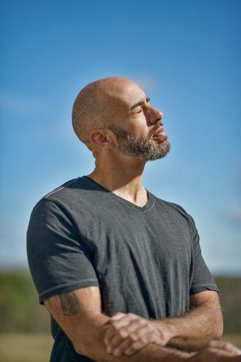 Man looking away against blue sky