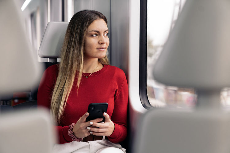 Mid adult man using mobile phone while sitting in train