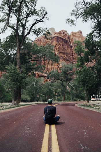 Rear View Of Man Sitting On Road Against Mountain