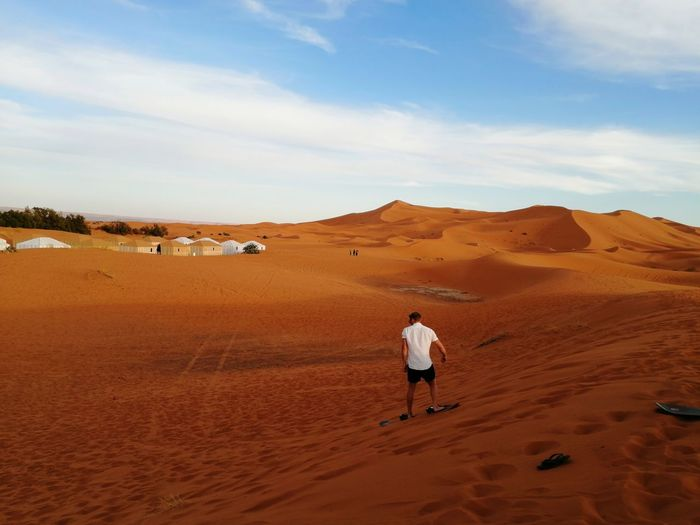 Rear view of man playing on desert against sky