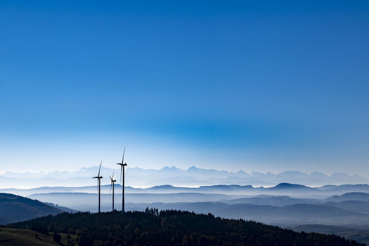Windmills On Mountain Against Blue Sky