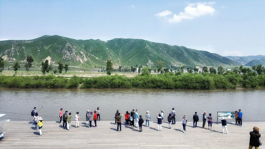 High angle view of people on promenade by river against sky