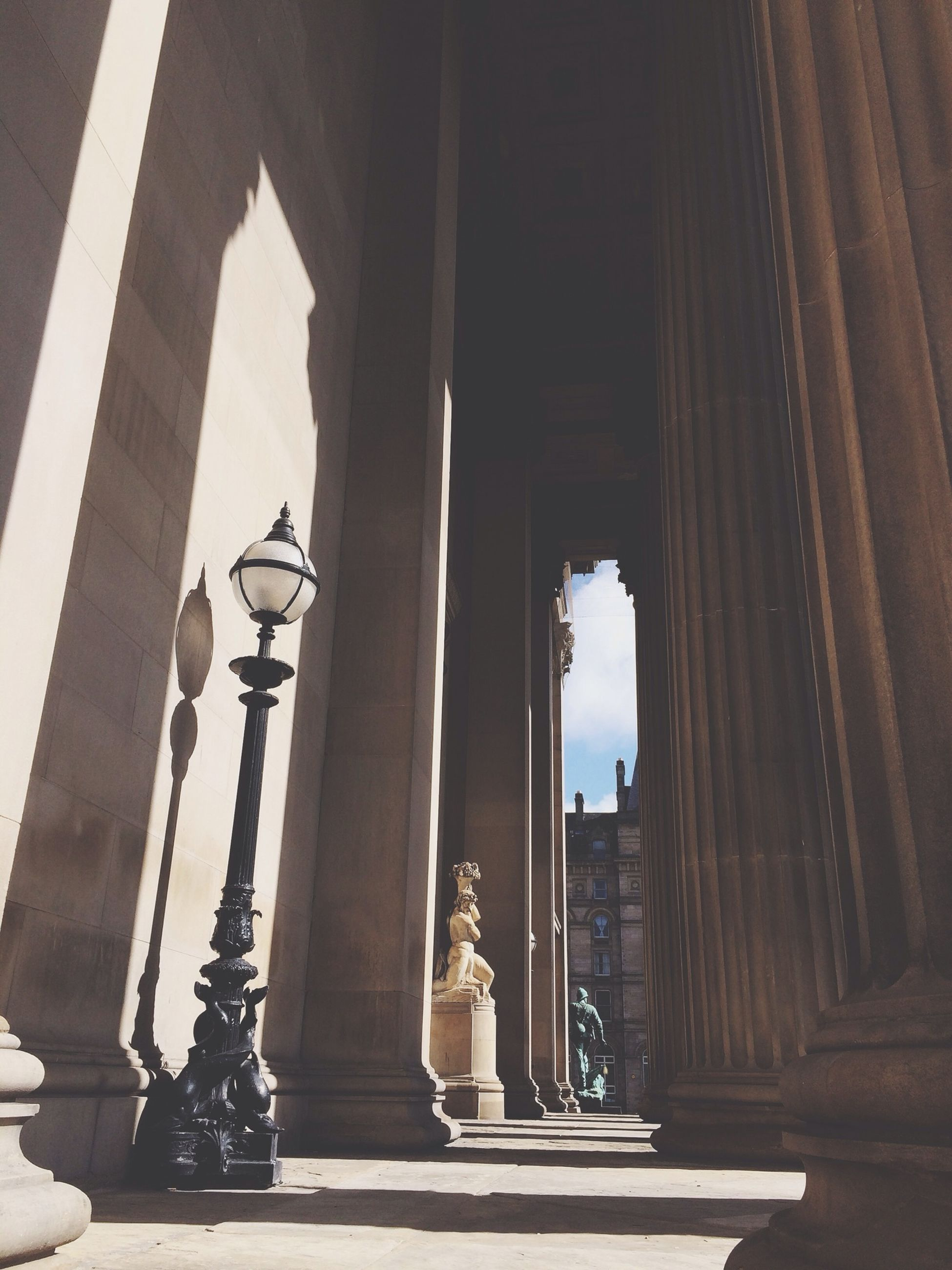 architecture, built structure, architectural column, statue, sculpture, indoors, arch, human representation, art and craft, column, art, building exterior, low angle view, history, day, creativity, sunlight, religion, entrance