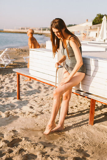 Full length of young woman at beach