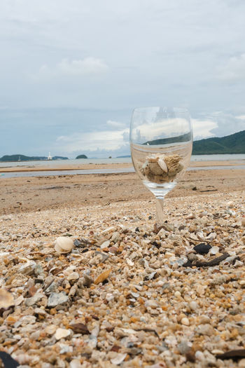 View of drinking glass on beach against sky