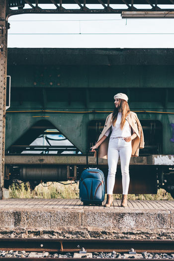 Full length of woman with train at railroad station platform