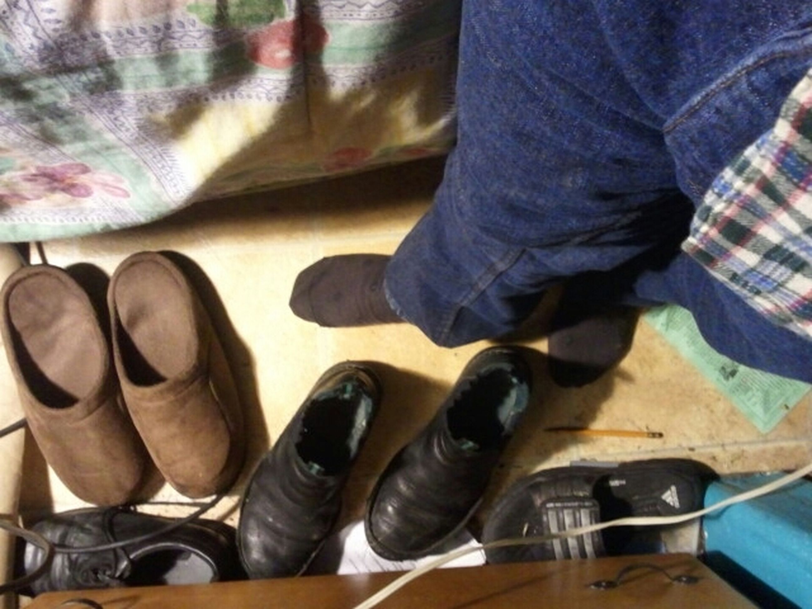 indoors, low section, person, shoe, jeans, footwear, men, lifestyles, high angle view, human foot, sitting, casual clothing, standing, canvas shoe, leisure activity, relaxation, personal perspective