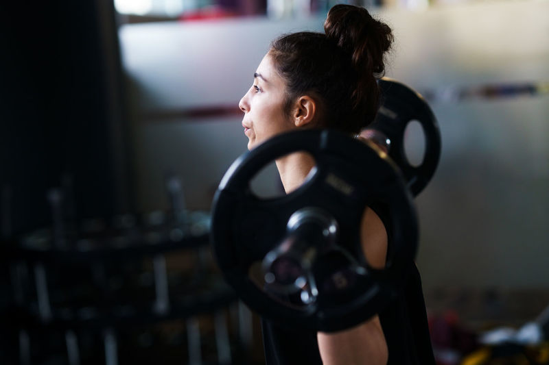 Side view of woman exercising with barbell in gym