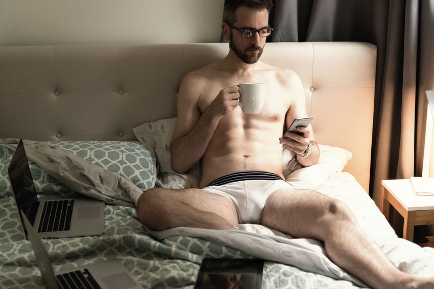 Handsome professional businessman in bed drinking coffee holding smart phone wearing only white underwear with computer laptops on the blanket. Caffeine Dating Morning Reading Testicular Cancer Awareness Bedroom Businessman Caucasian Coffe Computers Eyeglasses  Grooming Handsome Health Care Hotel Room Male Medical Research Middle Aged Mobile Phones Muscular Build Reproductive Health Skin Care Technology Testosterone Texting