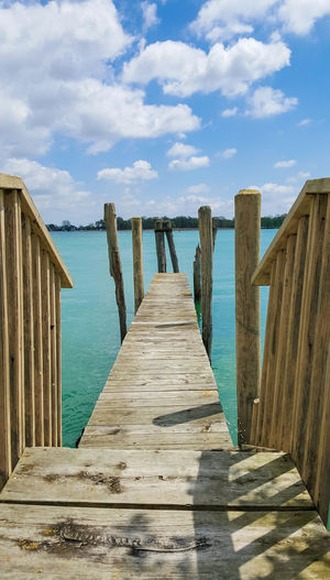 View of wooden jetty against cloudy sky