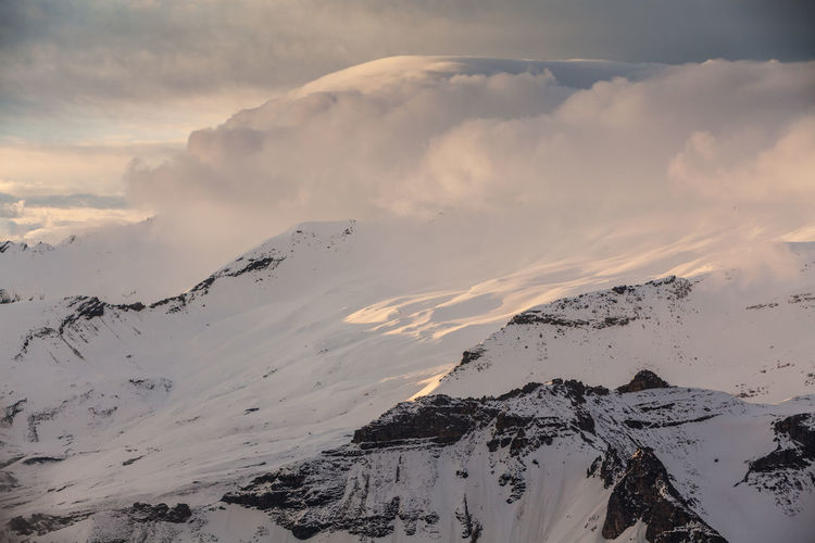 Aerial view of snow covered mountains against sky during sunset