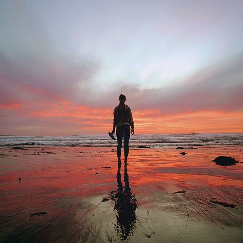 Man standing on beach against dramatic sky during sunset