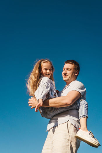 Low angle view of smiling father and daughter against